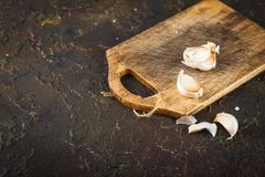 Garlic on Cutting Board. Garlic cloves on an old cutting board on a brown concrete background. Flat lay Stock Images