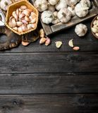 Garlic on a cutting Board with a garlic press. On black wooden background stock image