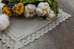 Garlic  with flowers and  linen napkin. Garlic decorated with dried  flowers and  green leaf of the plant ,close up Stock Image