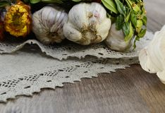 Garlic  with flowers and  linen napkin. Garlic decorated with dried  flowers and  green leaf of the plant ,close up Royalty Free Stock Image