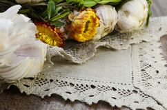Garlic  with flowers and  linen napkin. Garlic decorated with dried  flowers and  green leaf of the plant ,close up Royalty Free Stock Images