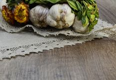 Garlic  with flowers and  linen napkin. Garlic decorated with dried  flowers and  green leaf of the plant ,close up Royalty Free Stock Photography