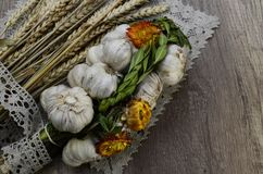 Garlic  with flowers and  and  linen napkin. Garlic decorated with dried  flowers and  green leaf of the plant ,close up.Top view Stock Photos