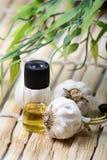 Garlic essence. Closeup shot of white garlic pods and essence bottle over wooden mat Stock Photo