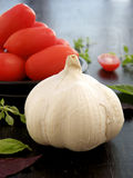 Garlic. Fresh garlic bulb on a table with tomatoes in the backround and basil leafs around Royalty Free Stock Photos