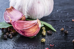 Garlic. Fresh Garlic. Cloves of garlic with parsley herb top leaves and pepper four colours Stock Photo