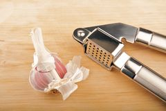 Garlic and garlic press. On woden surface Royalty Free Stock Images