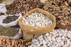 Garlic, ginger and spices in bags on a market Royalty Free Stock Images