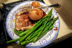 Garlic glazed pork chop with new potatoes and steamed asparagus spears royalty free stock image