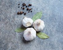 Garlic on the gray background. Garlic with bay leaves on the gray background Royalty Free Stock Photo