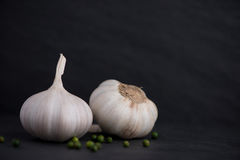 Garlic and green peppercorns on the black stone table Stock Photo