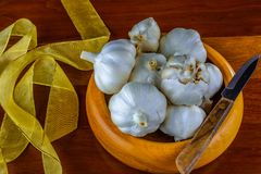 Garlic in hand turned hardwood bowl on a reclaimed hard wood background. Fresh organic garden garlic bulbs in a hand turned wooden bowl on a reclaimed hardwood Stock Photos