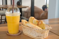 Garlic with herb bread and sweet yellow mango smoothie on wood table stock photo