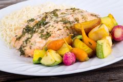 Garlic herb salmon with small vegetables. Garlic herb salmon with roasted small vegetables dish royalty free stock photos