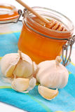 Garlic and jar of honey Royalty Free Stock Photography