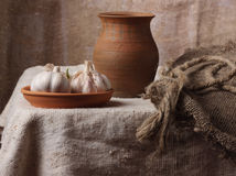 A garlic is a jug and sack. Garlic in a ceramic bowl, jug and sack Royalty Free Stock Photo