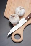 Garlic on kitchen cutting board Royalty Free Stock Photos