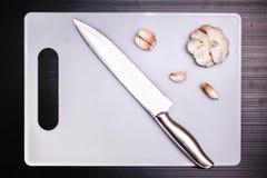 Garlic and knife on cutting board Stock Image