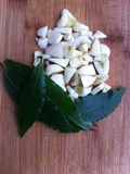 Garlic and laurel. Cuted garlic and laurel on the wooden board Royalty Free Stock Images