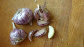 Heads of garlic on a wooden Board lie on the table. Whole bulb of peeled red or purple striped garlic scattered cloves on wooden royalty free stock image
