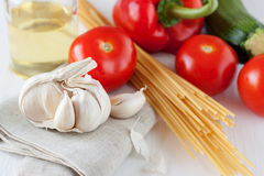Garlic on linen napkin with vegetables Stock Image
