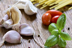 Garlic, mint, cherry tomatoes and spaghetti. Closeup of some garlics, a twig of mint, some cherry tomatoes and a pile of uncooked spaghetti on a rustic wooden Royalty Free Stock Photography