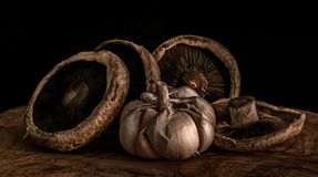 Garlic and mushrooms. A bulb of garlic and mushrooms on an olive wood board Royalty Free Stock Photography