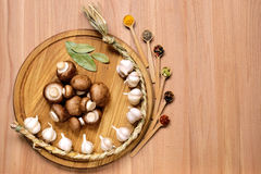 Garlic, mushrooms and spice on wooden table. Royalty Free Stock Photos