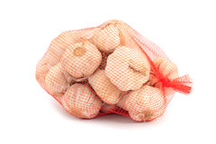 Garlic in a net over white Royalty Free Stock Photos