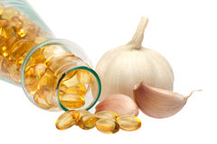 Garlic and oil capsule. On white Stock Images