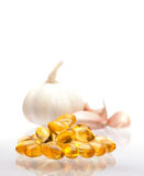 Garlic and oil capsule. On white Stock Photos