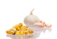 Garlic and oil capsule. On white Royalty Free Stock Photos