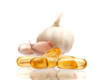 Garlic and oil capsule. On white Royalty Free Stock Photo