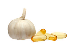 Garlic and oil capsule. On white Royalty Free Stock Image