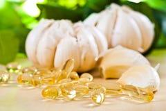 Garlic oil. Capsules and garlic stock photos