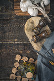 Garlic , olive oil and kitchen accessorize on the wooden table vertical. Garlic , olive oil , salt and pepper shaker , napkin , fork and knife on the wooden Royalty Free Stock Photography