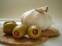 Garlic and olives. Garlic and green olives stuffed with paprika Stock Images