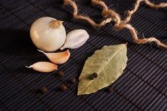 Garlic, onion, bay leaf, black pepper on black table. Food background. Garlics. sliced garlic, garlic clove, garlic bulb. Garlic, onion, bay leaf, black pepper stock photos