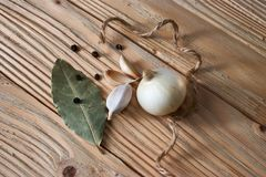Garlic, onion, bay leaf, black pepper on a wooden table. Food background. Garlics. sliced garlic, garlic clove, garlic bulb. Garlic, onion, bay leaf, black stock photo
