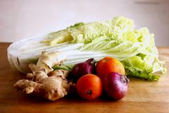 Garlic, onion, ginger, tomato and cabbage on a chopping board Royalty Free Stock Images