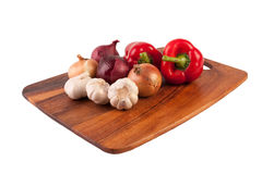 Garlic, onion and pepper on cutting board. Isolated on white Royalty Free Stock Photo
