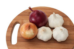 Garlic, onion and red onion on wooden kitchen board Stock Photos