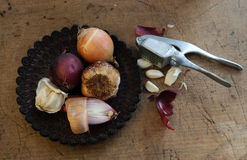 Garlic and Onion on Rustic Plate Stock Images