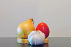 Garlic, onion and tomato on table Royalty Free Stock Photos