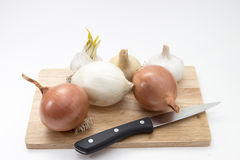 Garlic and onion on a wooden board with knife Royalty Free Stock Photography