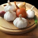 Garlic and onions on cutting board Stock Images