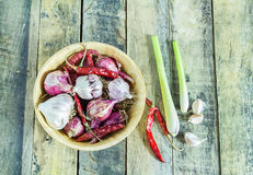 Garlic,onions,dry pepper and lemon grass in wooden bowl on wood Royalty Free Stock Images