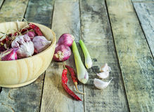 Garlic,onions,dry pepper and lemon grass in wooden bowl on wood Stock Images