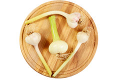 Garlic and onions heads on a chopping board Royalty Free Stock Image