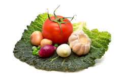 Garlic, onions, peas, tomatoes on a cabbage leaf Royalty Free Stock Photography
